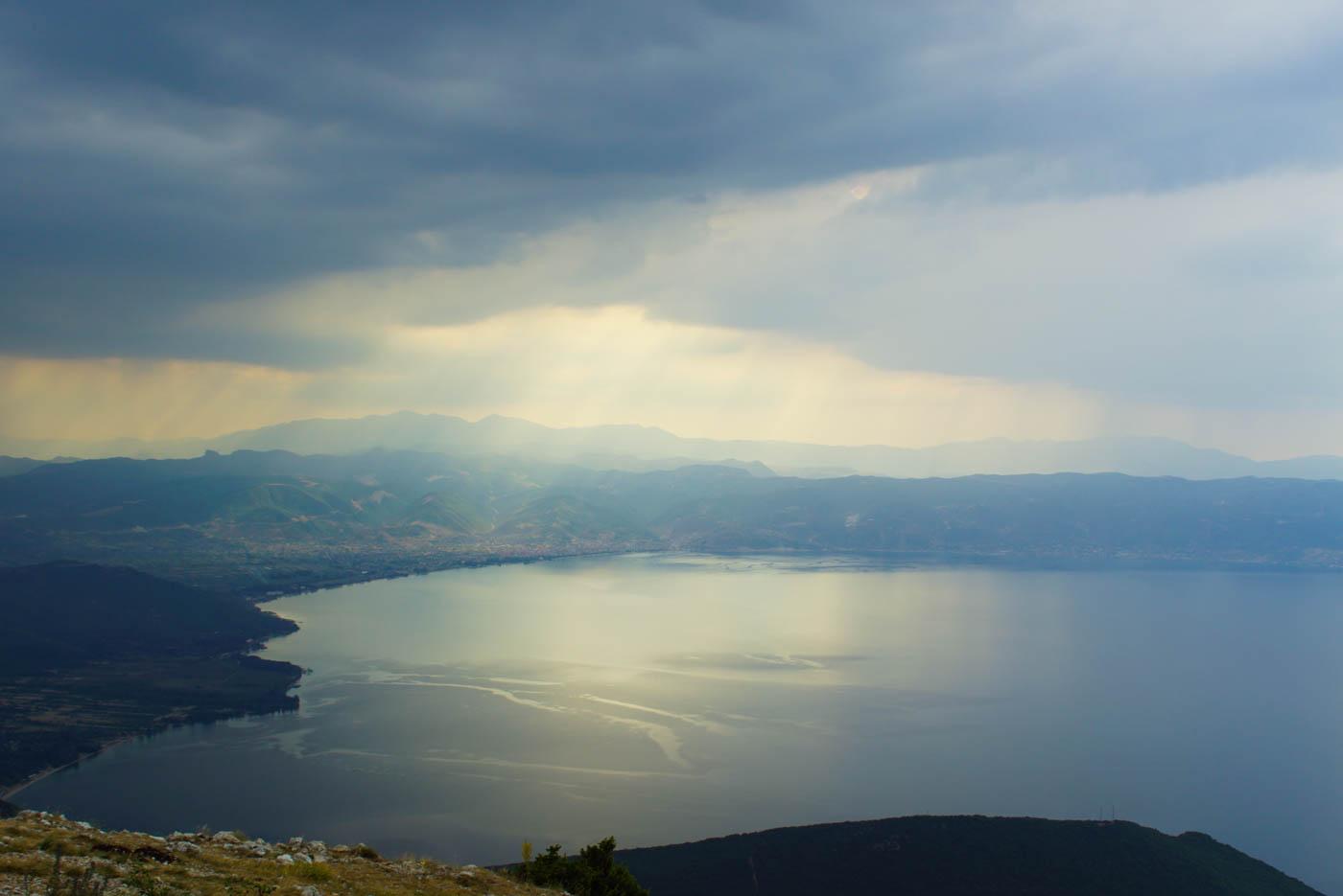 Wundervoller Blick auf den Ohridsee von den Bergen aus. Es zieht gerade eine Regen Flake hinüber die von der Sonne beschienen wird im Hintergrund weit entfernt ist eine Stadt zu erkennen.