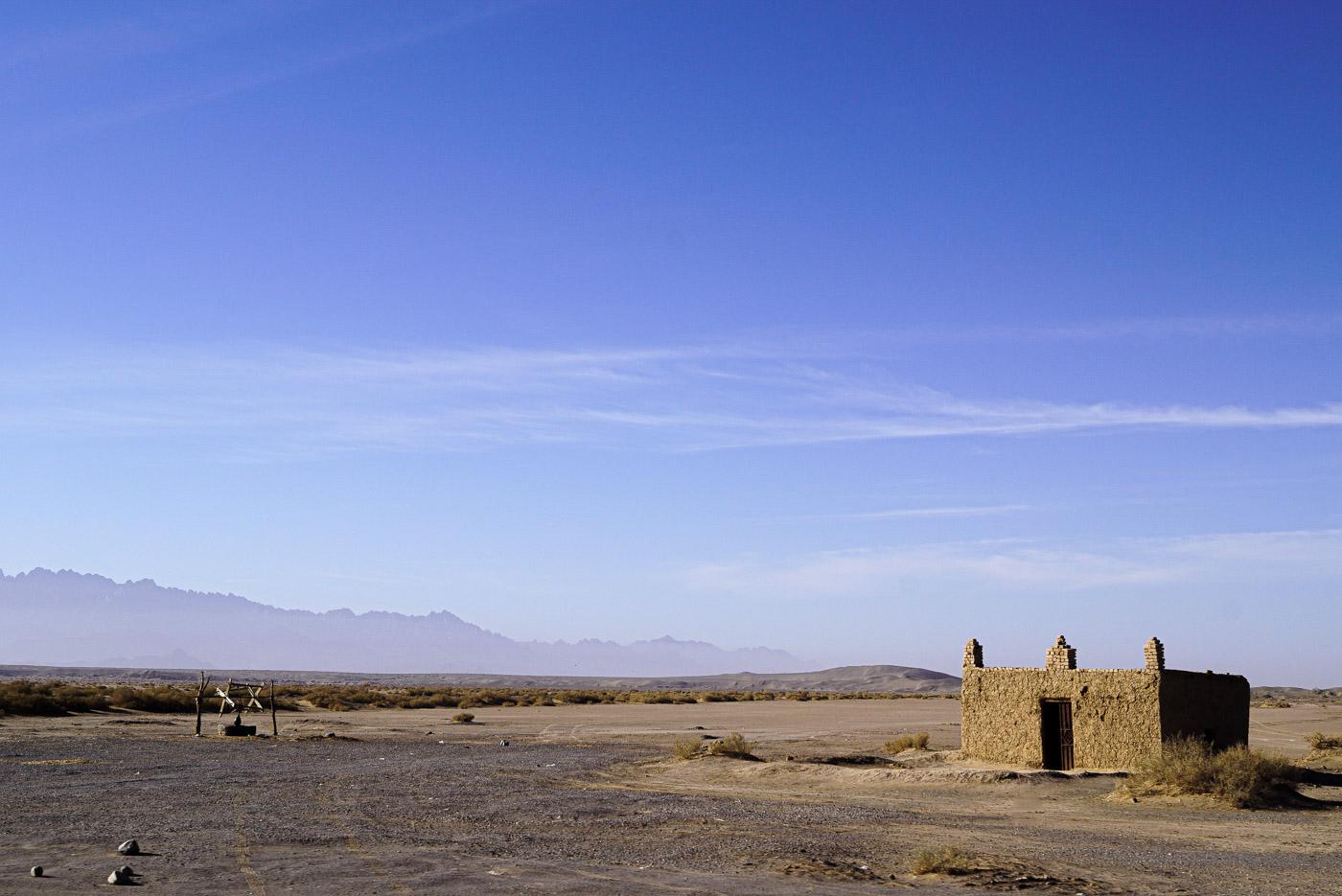 Zu sehen ist eine Steppe, weit im Hintergrund erheben sich schroffe Bergformationen. Auf der linken Seite ist ein Brunnen zu sehen mit einem Rad mit dem ein Wassersack hoch und runtergezogen werden kann. Am linken Bildrand ist ein kleines Leben Haus zu sehen, welches drei Verzierungen auf dem Dach aufweist.