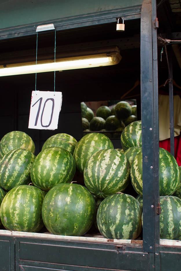An einem Stand werden Wassermelonen angeboten. Es sind 3 Reihen mit jeweils 4 Melonen zusehen die übereinandergestapelt sind. Ein Schild besagt, dass sie 10 Dinar das Kilo Kosten