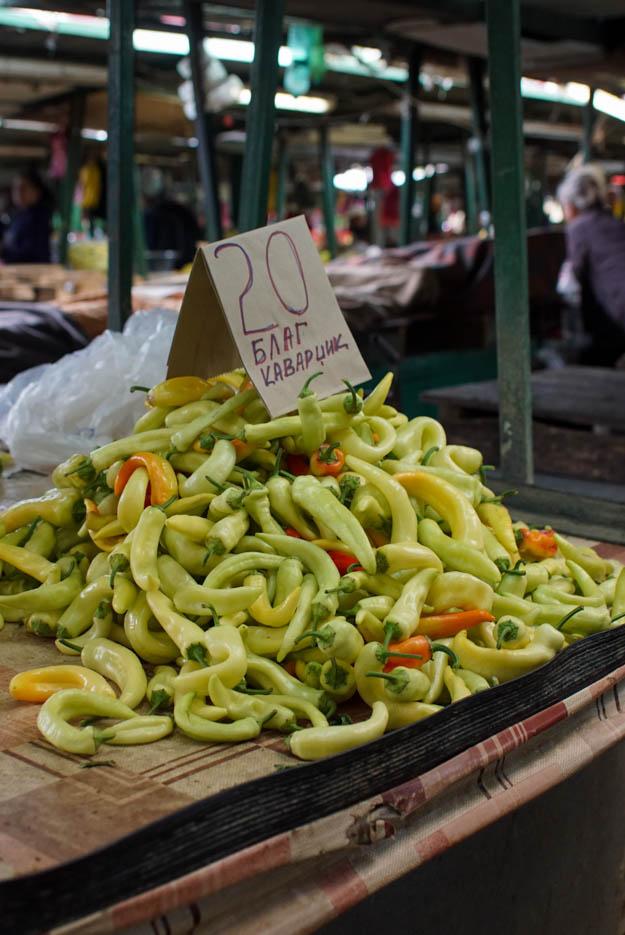 auf einem Markt ist ein Haufen von hellgelben Peperonis zu sehen, auf ihnen steht ein Schild das besagt, dass sie für 20 mazedonische Dinar das Kilo angeboten werden