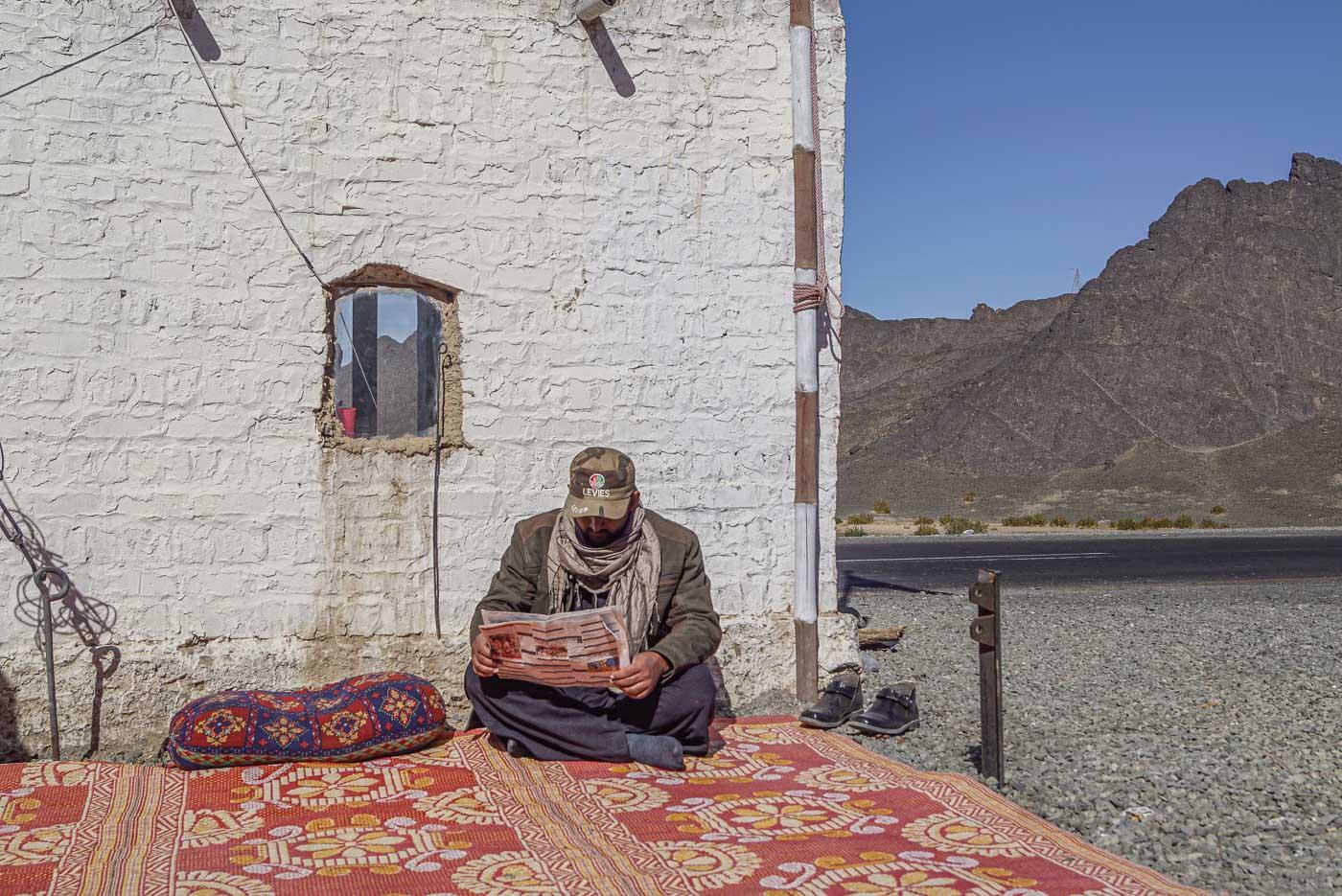 Zu sehen ist wie ein Levie mit ausgezogenen Schuhen auf einem bunten Teppich sitzt. Im Hintergrund ist ein Lehmhaus zu sehen und dahinter erstrecken sich die wunderschönen Berge von Belutschistan. Der Levie blickt nach unten und liest Zeitung