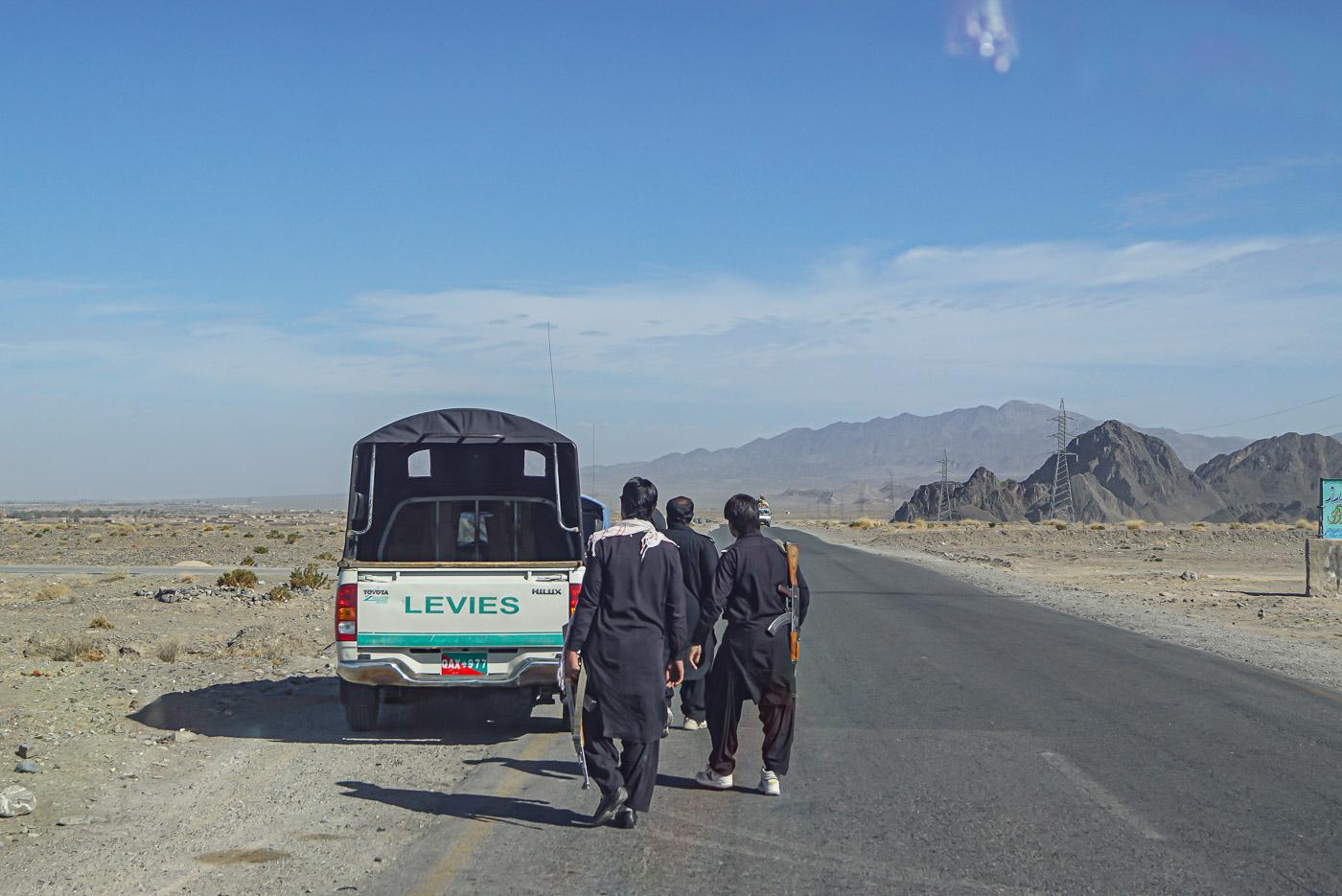 Zu sehen ist die karge Landschaft mit Bergen im Belutschistan. Im Vordergrund steht ein Jeep unserer Eskorte Am Straßenrand laufen vier Levi's mit Kalaschnikow nach einem Stopp zurück zu ihrem Auto um sich für die Weiterfahrt bereit zu machen.