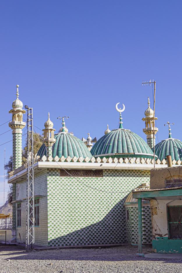 Zu sehen ist eine kleine Moschee mit winzigen Minaretten und drei Kuppeln, auf der einen Kuppel in der Mitte befindet sich ein goldener Halbmond die ganze Moschee ist mit grünen und weißen Kacheln verziert.