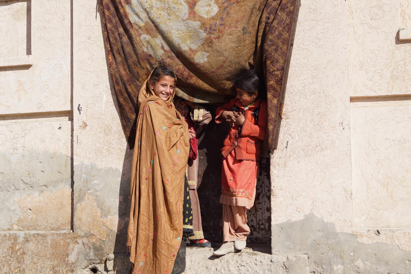 In der Polizei Enklave von Quetta stehen vor einem Hauseingang der mit einem Vorhang bedeckt ist, drei Mädchen und lachen herzlich in die Kamera. Das eine Mädchen hat ein sehr ausdrucksstarkes Gesicht. Alle drei sind mit traditionellen pakistanischen Gewändern bekleidet.