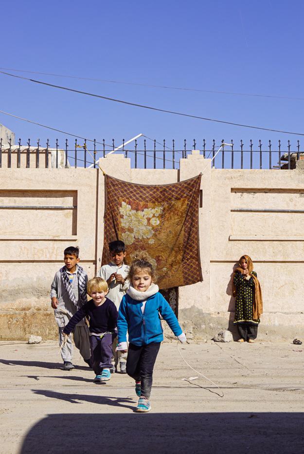 Luk und ein argentinische Mädchen Rennen auf die Kamera zu. Dahinter stehen zwei pakistanische Jungen und schauen zu. Ganz im Hintergrund ist ein Hauseingang zu sehen der mit einem Teppich verhangen ist, daneben steht ein Mädchen mit Kopftuch und traditionellem Gewand und schaut den spielenden Kindern zu.