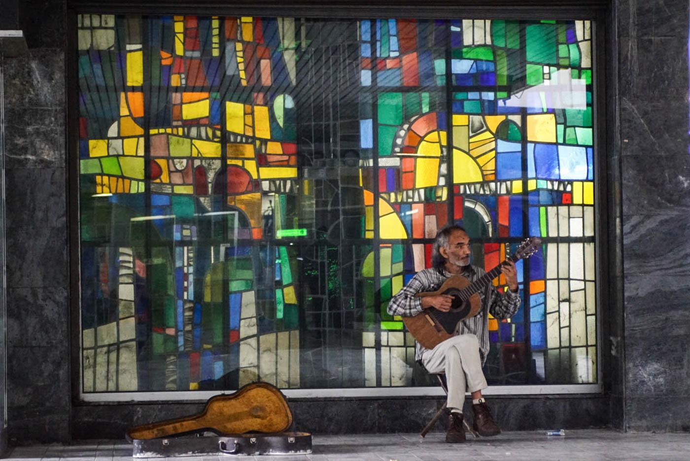 Zu sehen ist ein großes Buntglasfenster das an Hundertwasser erinnert, davor sitzt ein Straßenmusikant und spielt Gitarre