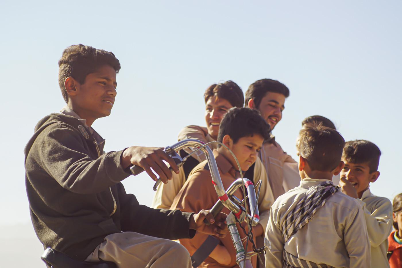 Im Vordergrund ist ein pakistanischer Junge auf einem Fahrrad zu sehen welches einen hohen Lenker hat im Hintergrund lachen und scherzen sechs andere Jungen alle tragen wiederum traditionelle pakistanische Kleidung.