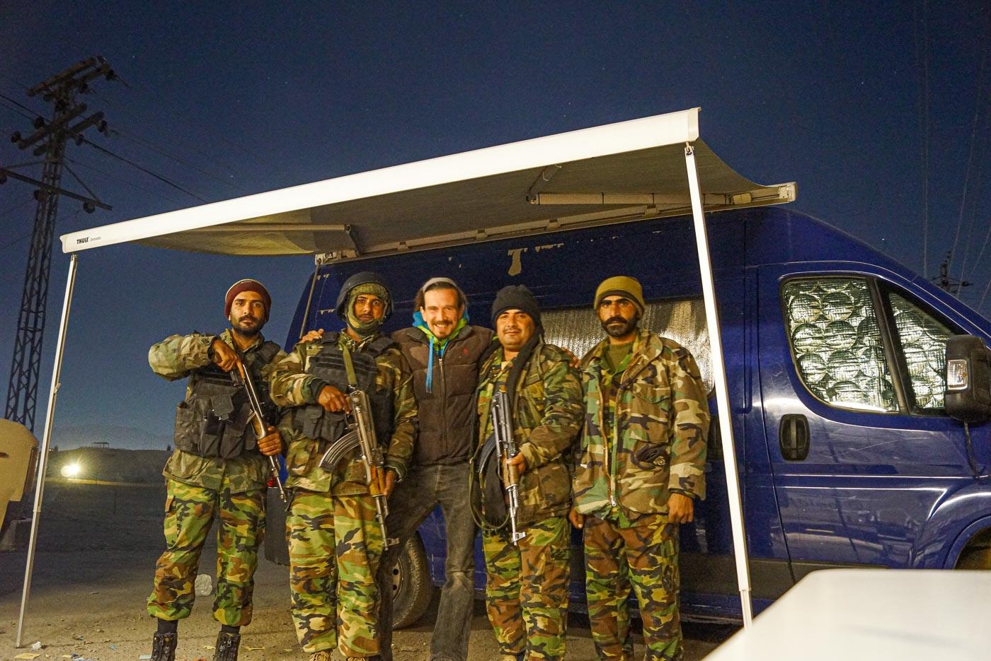 Zu sehen ist unser Bus mit ausgefahrener Markise darunter steht Paul mit vier schwerbewaffneten Soldaten und lächelt in die Kamera.