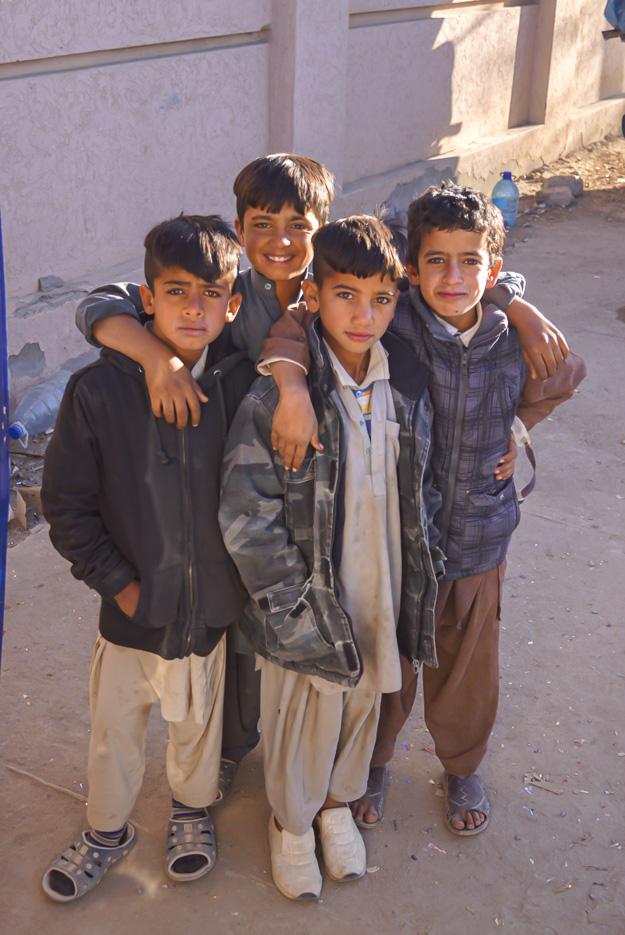 Vier ca. zehn Jahre alte pakistanische Jungs halten sich im Arm und Lächeln in die Kamera. Alle vier haben einen sehr intensiven Blick.