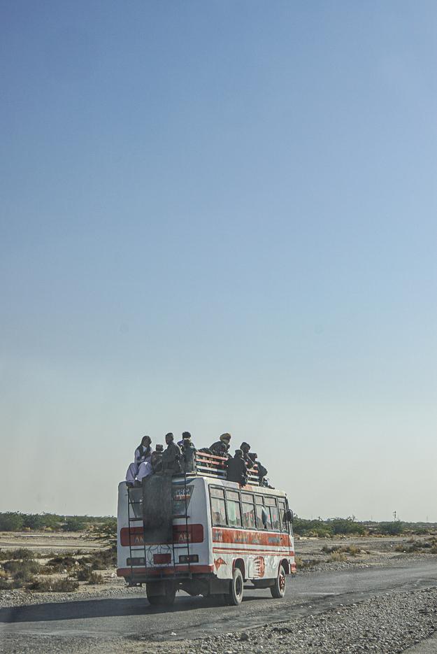 Zu sehen ist wie ein verzierter pakistanischer Laster voll beladen durch die Landschaft fährt. Auf seinem Dach sind Gepäck und zehn weitere Personen teilweise mit Turban.