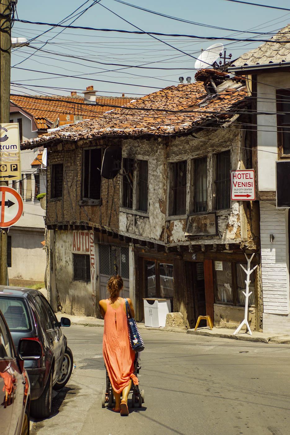 Lea läuft mit Kinderwagen und orangefarbenem Kleid eine Straße hinunter direkt vor ihr ist ein sehr altes Haus zu sehen was in der Mitte im ersten Stock durchgesackt ist