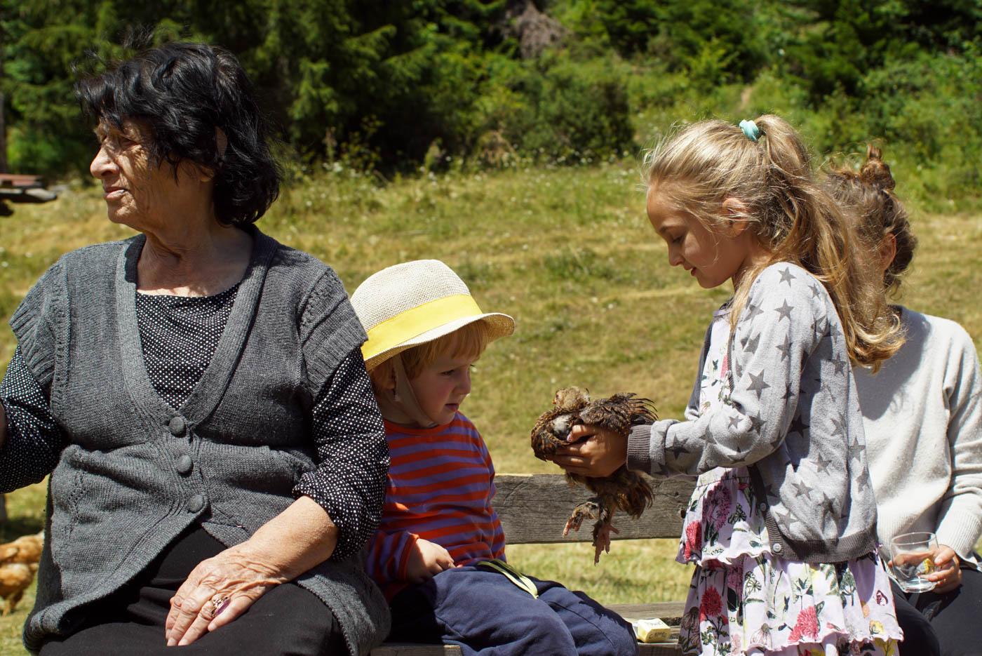 Luke sitzt auf einer Bank neben einer alten Frau mit zerfurcht im Gesicht ein Mädchen reicht ihm ein Küken