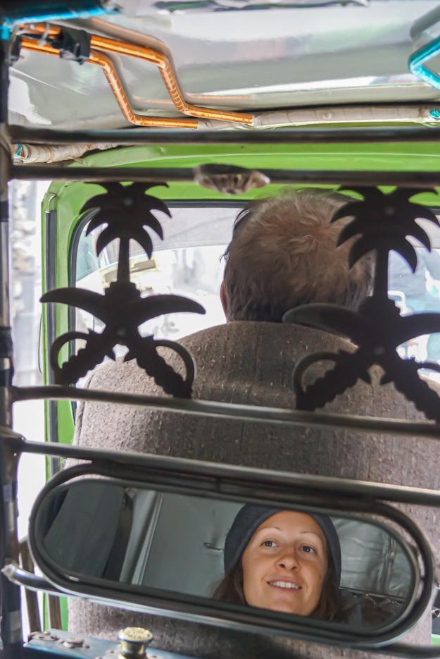 Zu sehen ist das Innere einer Rikscha wobei an der Trennung zum Fahrer Häuschen ein Spiegel angebracht ist in den Lea zu sehen ist. Dahinter sieht man den Fahrer die Rikscha durch den chaotischen Stadtverkehr lenken.