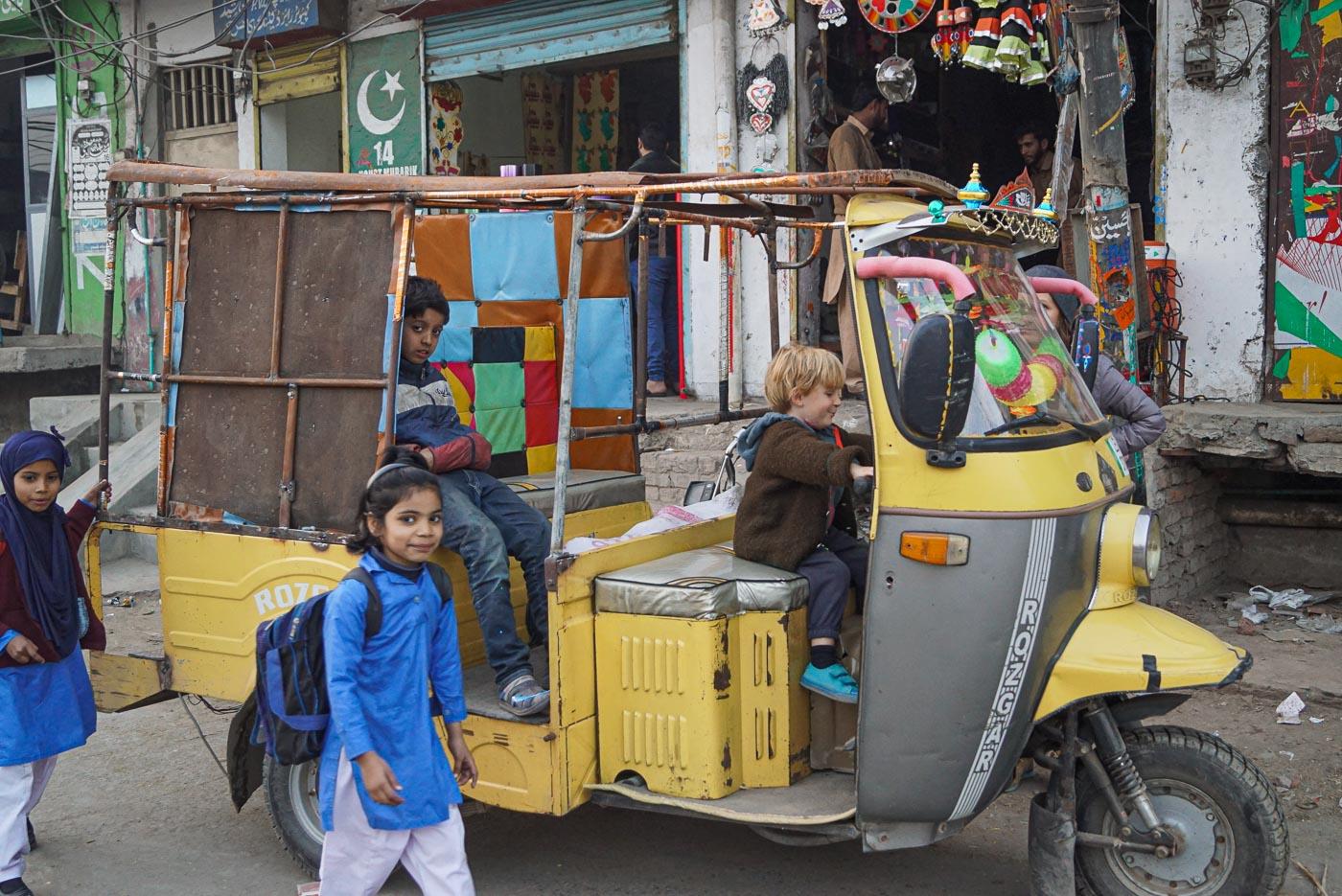 Zu sehen ist wie Luk am Steuer einer gelben Rikscha sitzt auf den Fahrgastbank sitzt ein pakistanischer Junge und schaut in die Kamera. Im Vordergrund läuft ein Mädchen ohne Kopftuch vorbei und da hinten ein kleines mit.
