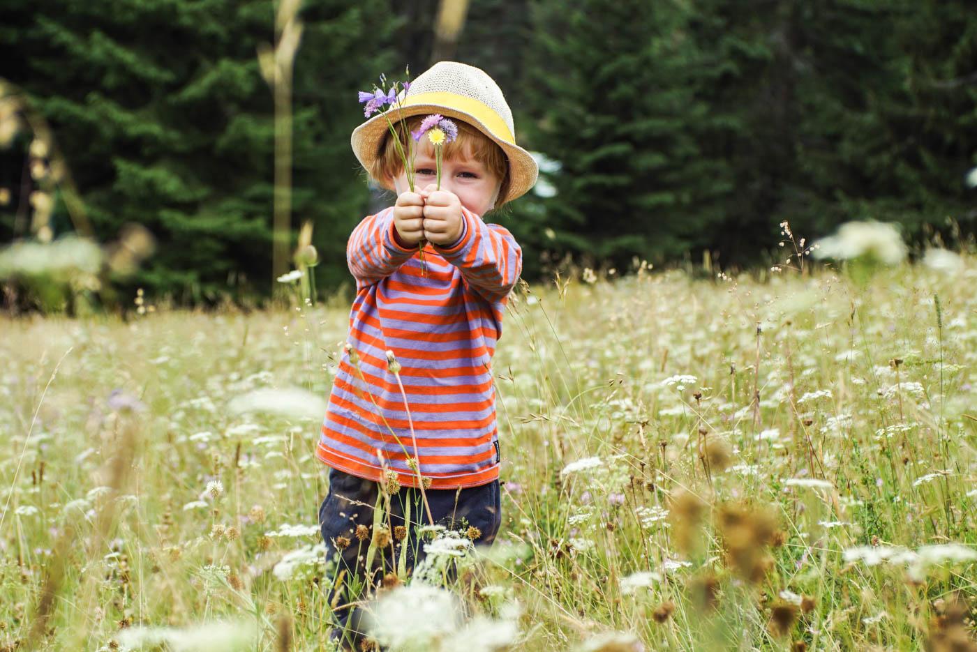 Luke steht auf einer bergblumenwiese und hält zwei kleine Blumensträuße vors Gesicht