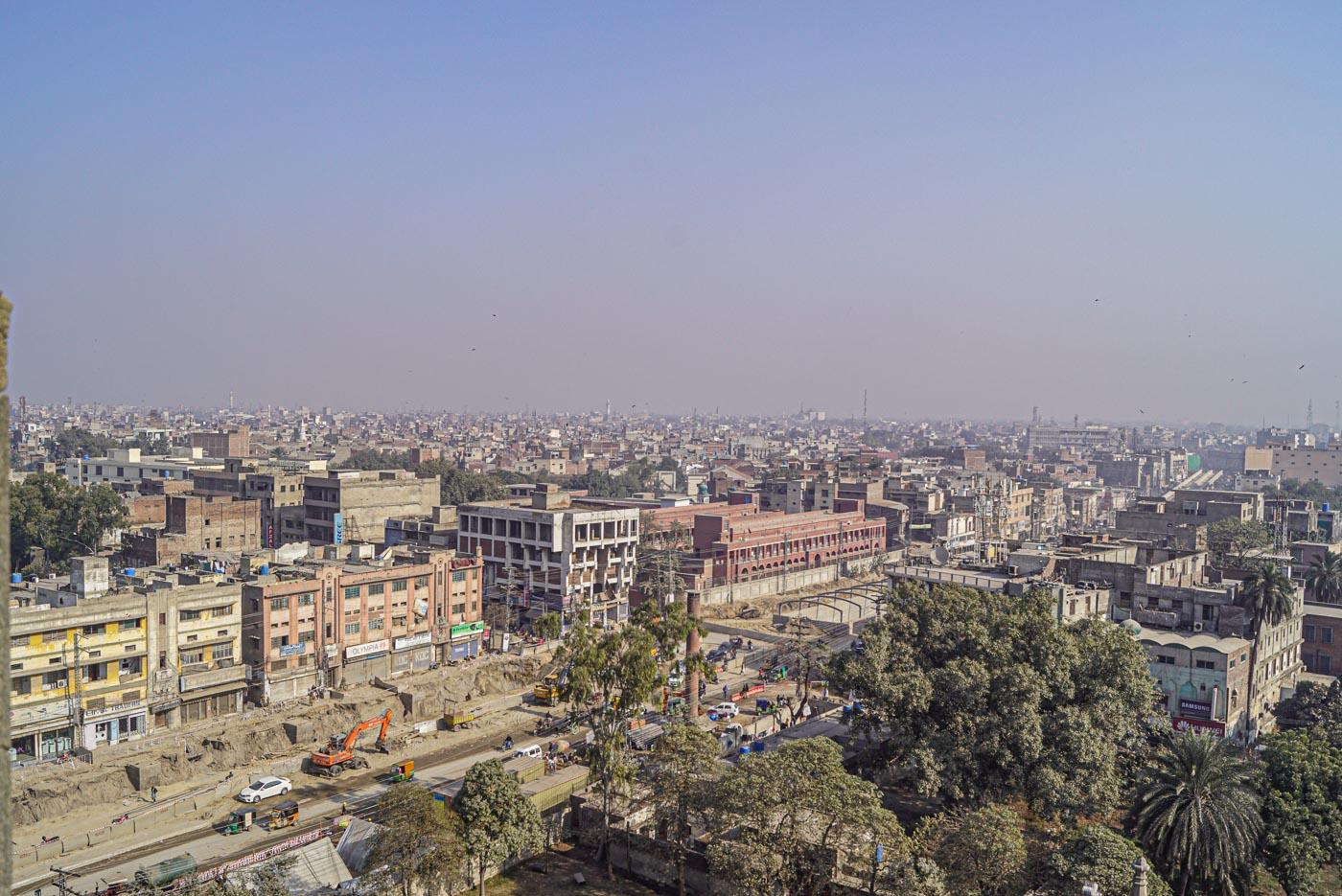 Blick über die Stadt Lahore von dem Kirchturm der Kathedrale. Viele Häuser erstrecken sich bis an den Horizont und bilden ein schönes Mosaik, im Vordergrund wird ein Tunnel gebaut.