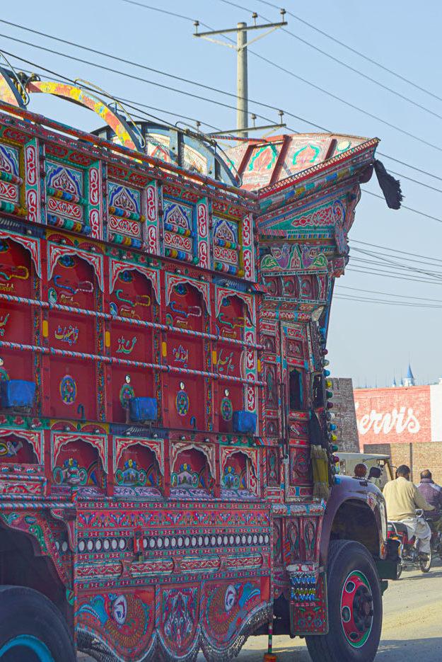 zu sehen ist ein alter Lastwagen in typischer pakistanischer Verzierung die Hauptfarben sind rot und blau. Ein hoher Aufbau erhebt sich über dem Fahrerhaus der wiederum zahlreiche detaillierte reliefartige Verzierungen aufweist.