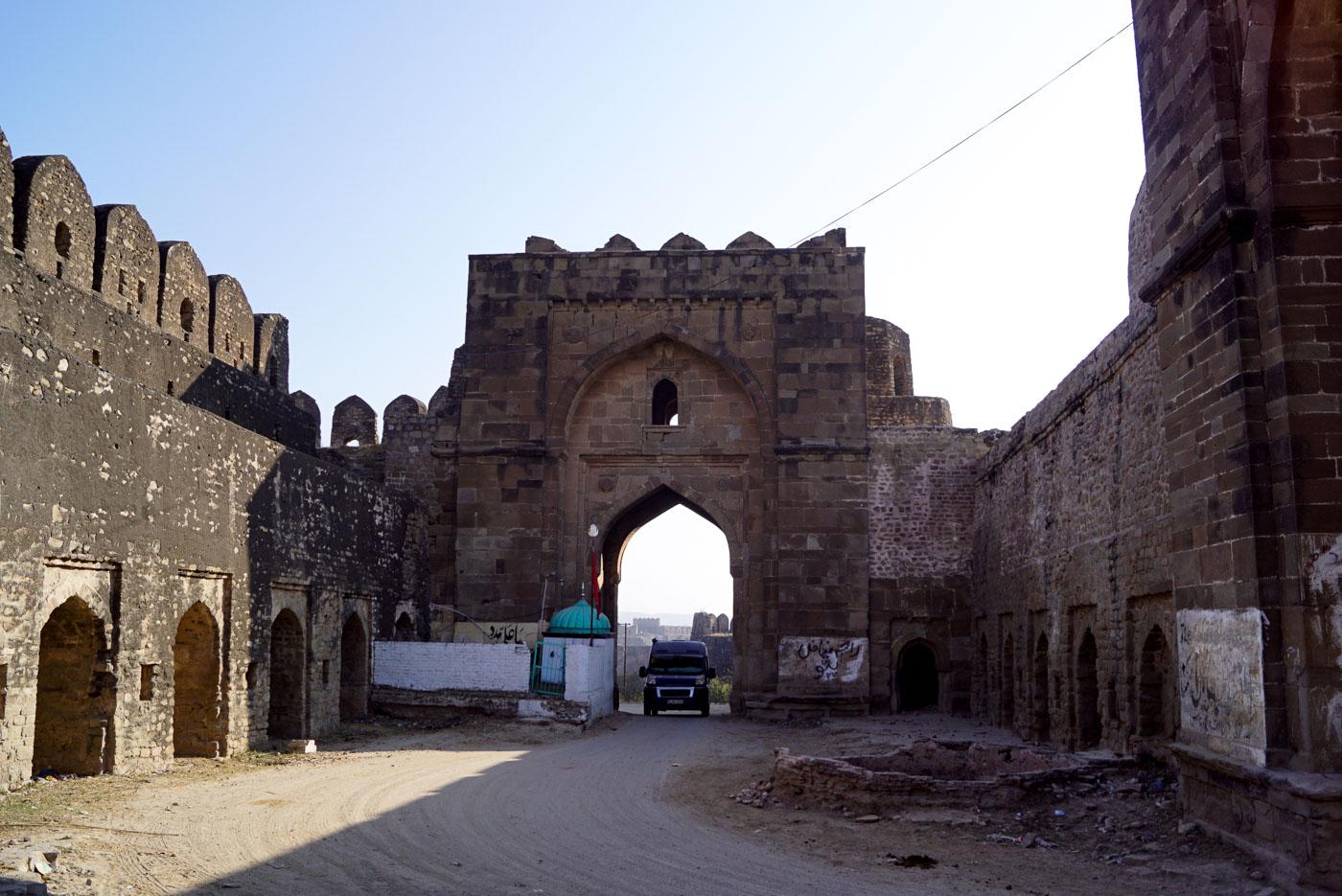 Zu sehen ist wie wir mit dem Auto durch eines der monumentalen Tore des Rohtas Fort fahren.