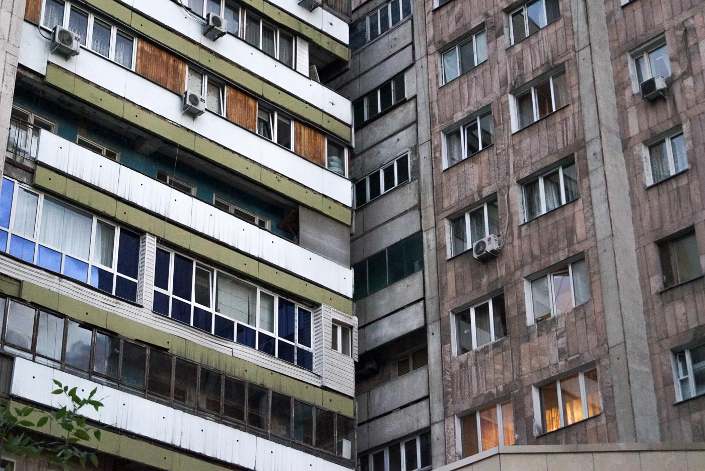 zu sehen sind zwei Plattenbauten die dicht nebeneinander gebaut sind und so ein Dreieck bilden ihre Häuserfronten sind grau und teilweise grün in den Fenstern spiegelt sich der Himmel wider.