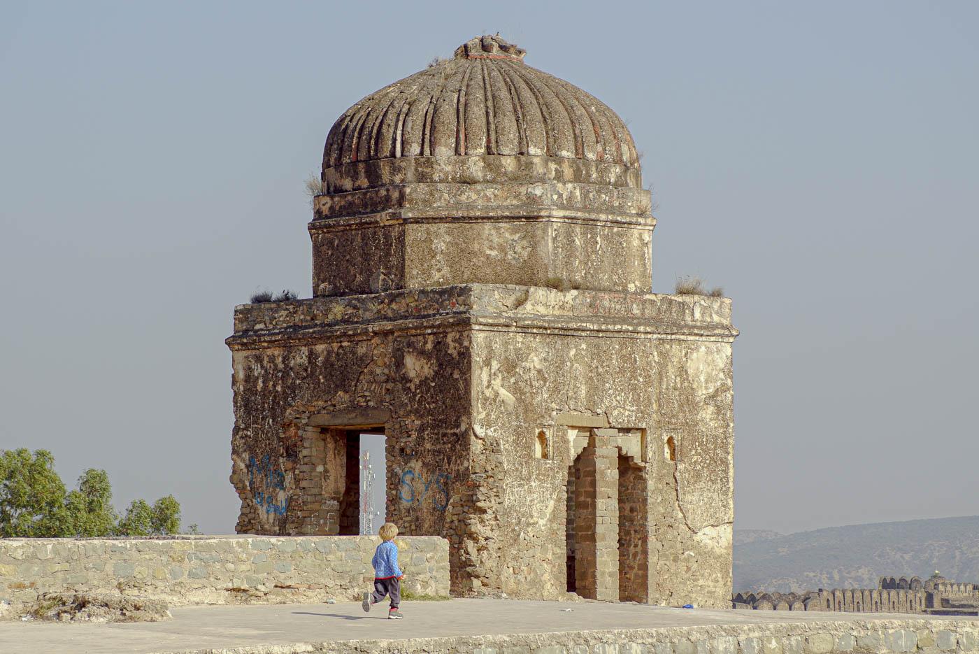 Zu sehen ist Luk, wie er über die gigantisch großen Mauer Anlage des Rohtas Fort rennt. Die Mauer erstreckt sich am unteren Bildrand weiter fort. In der Mitte des Bildes erhebt sich ein Turm.