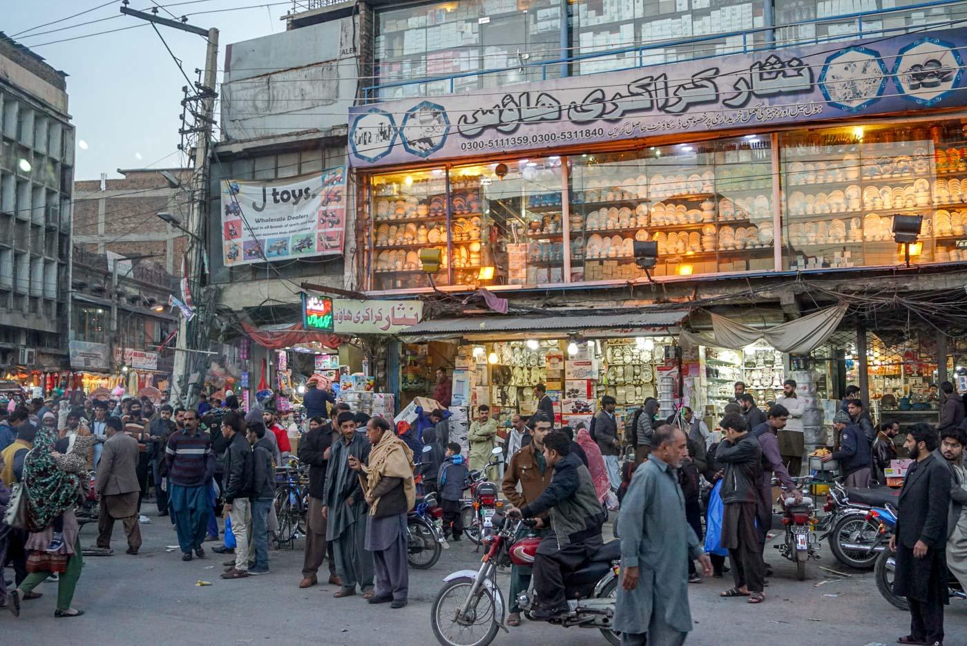 Zu sehen ist das chaotische treiben auf den Straßen von Rawalpindi. im Vordergrund sind hauptsächlich jede Menge Männer zu sehen die sich unterhalten. Im Hintergrund erhebt sich ein großes Geschäft mit zwei Stockwerken in denen Porzellan Ware im Schaufenster zu sehen sind.