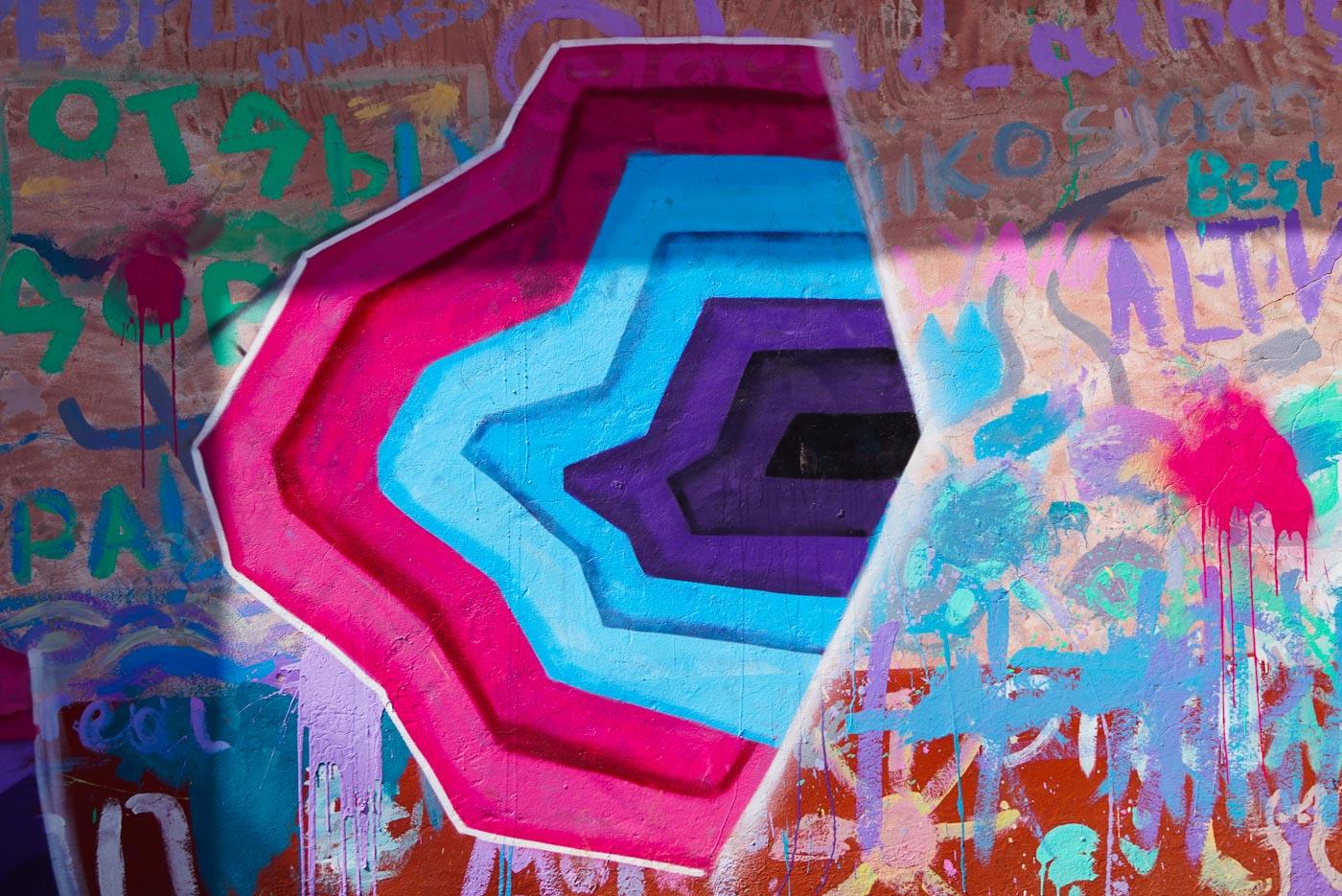 zu sehen ist ein buntes Graffiti die Hauptfarben sind rosa hellblau und lila es wird eine geometrische Form dargestellt die einen Tunnelblick erzeugt.