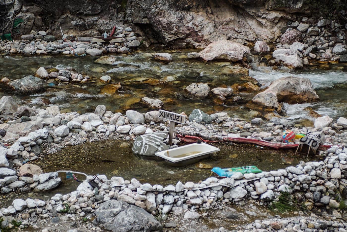 Zu sehen ist wie in einem Fluss mit auf gehäuften Steinen ein künstliches Becken gebildet wurde in der Mitte steht eine Badewanne mit einem Schild dahinter auf dem Jacuzzi steht.