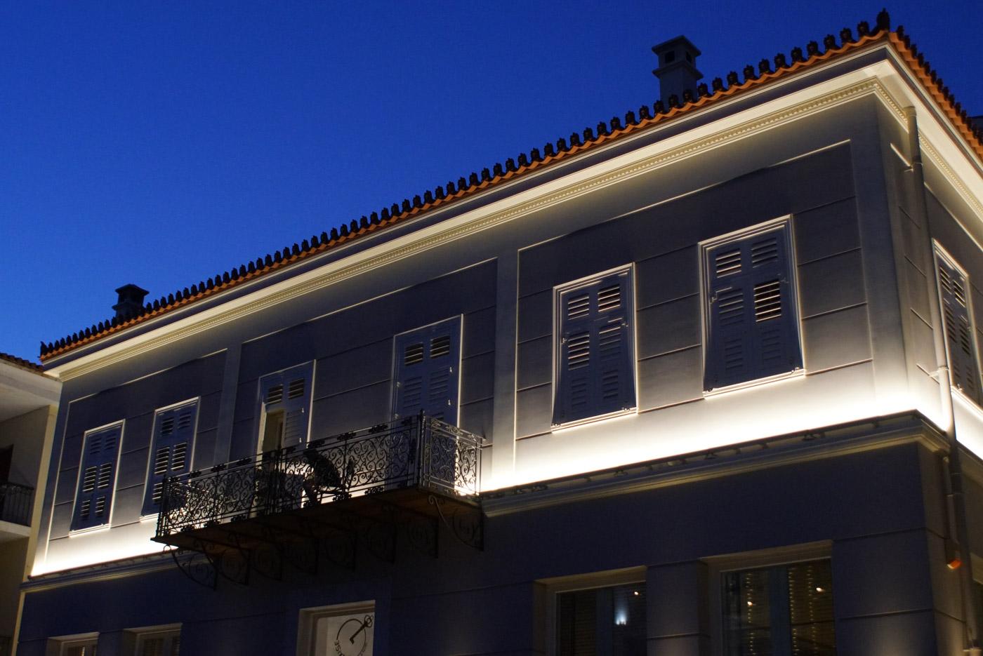 Eine klassizistische zweistöckige Häuserfront die vom ersten Giebel nach oben beleuchtet wird. Der erste Stock liegt im Dunklen der Himmel über dem zweiten ist kobaltblau