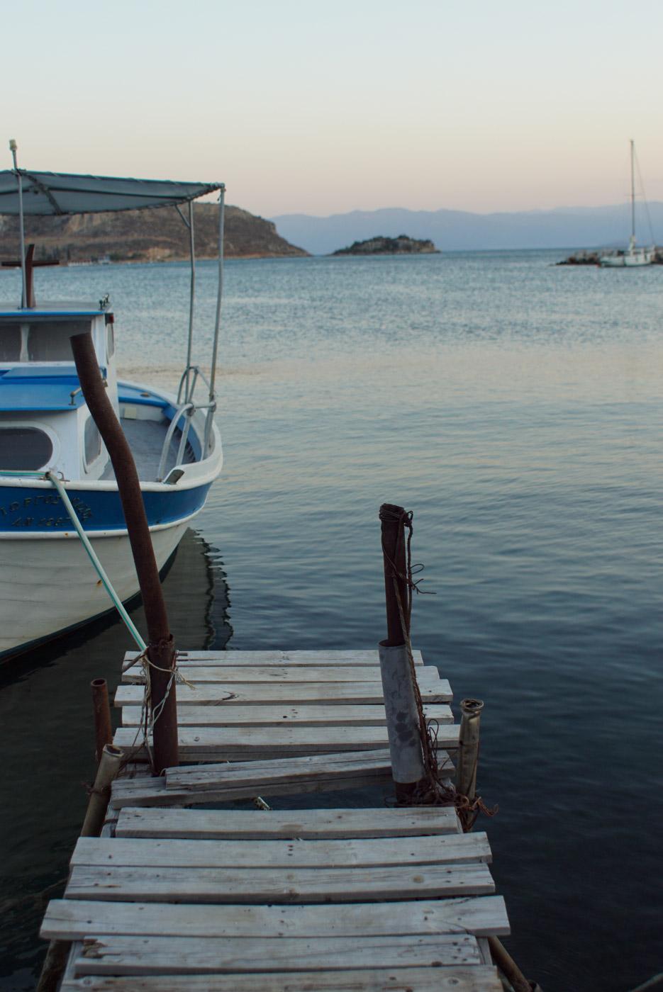 Blick von einem alten maroden Holzsteg in die Bucht auf der linken Seite deshalb ein kleines Fischerboot zu erkennen rechts in der Ferne ein Segelboot das vor Anker liegt