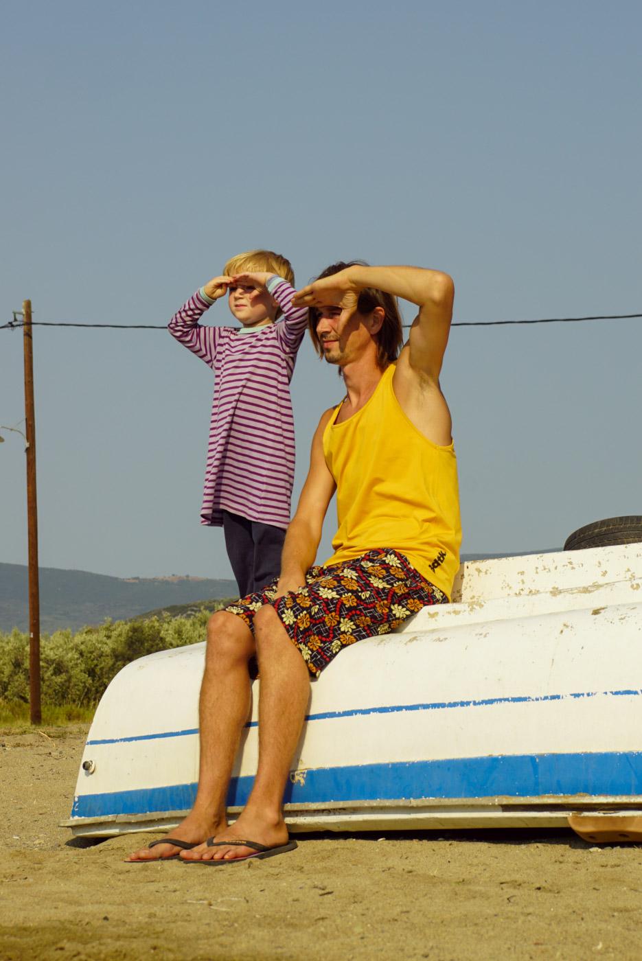 Luk steht auf einem umgedrehten kleinen Ruderboot und Paul sitzt neben ihm. Beide bedecken sich die Augen vor der Sonne und blicken in die Ferne.