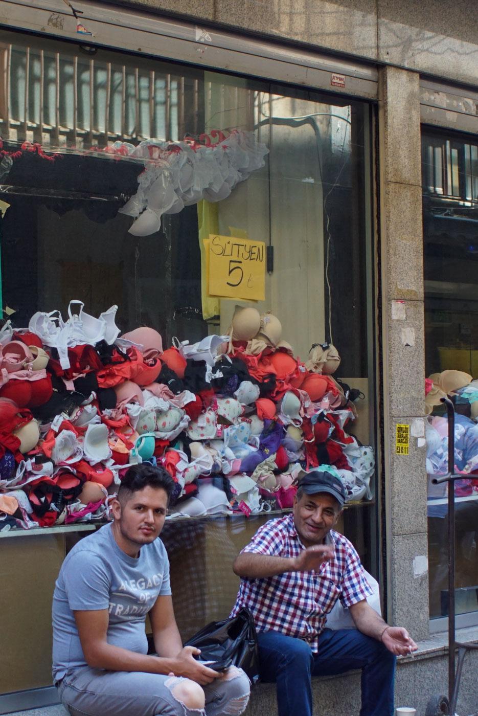Zwei Männer sitzen vor einer Ladenfront und Lachen in die Kamera. Hinter ihnen ist ein Schaufenster voll mit BHs und einem Schild, dass diese 5 Lira der Stückkosten.