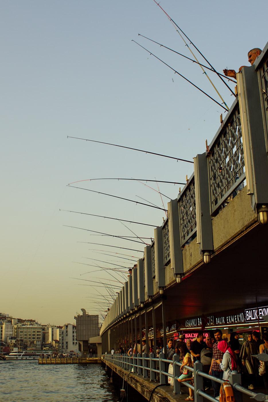 Blick vom Ufer auf die Galata Brücke in Istanbul. oben am Geländer stehen unzählige Handler über die gesamte Länge der Brücke Punkt im Untergeschoss der Brücke sind Touristen zu sehen die auch das Wasser gucken hinter ihnen sind zahlreiche Restaurants.