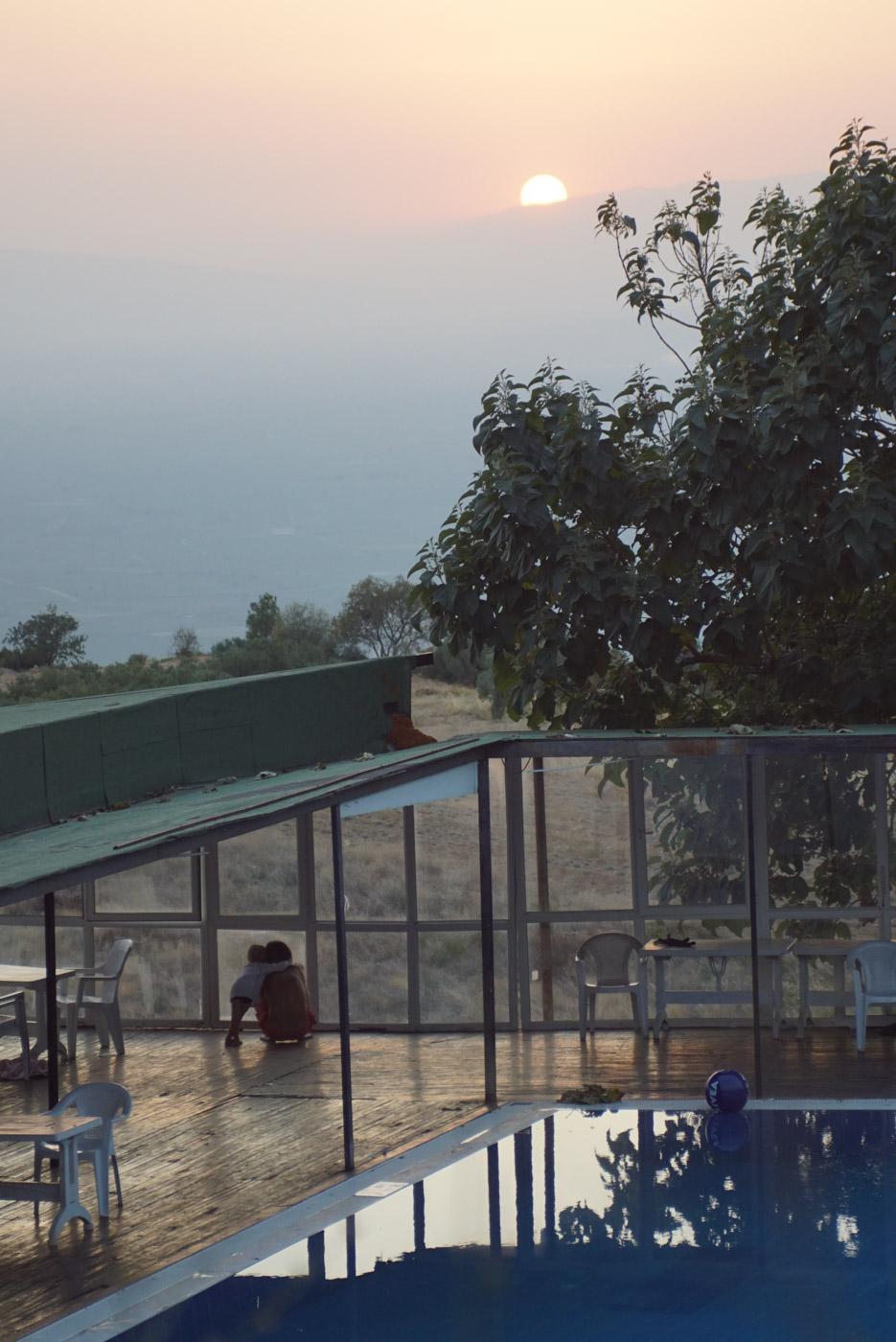 In der Nähe von amukkale Punkt im Vordergrund ist ein Swimmingpool zusehen dahinterstehen Paul und Luke unter einer Veranda und blicken in dem Horizont wo gerade die Sonne hinter einem Berg verschwindet.