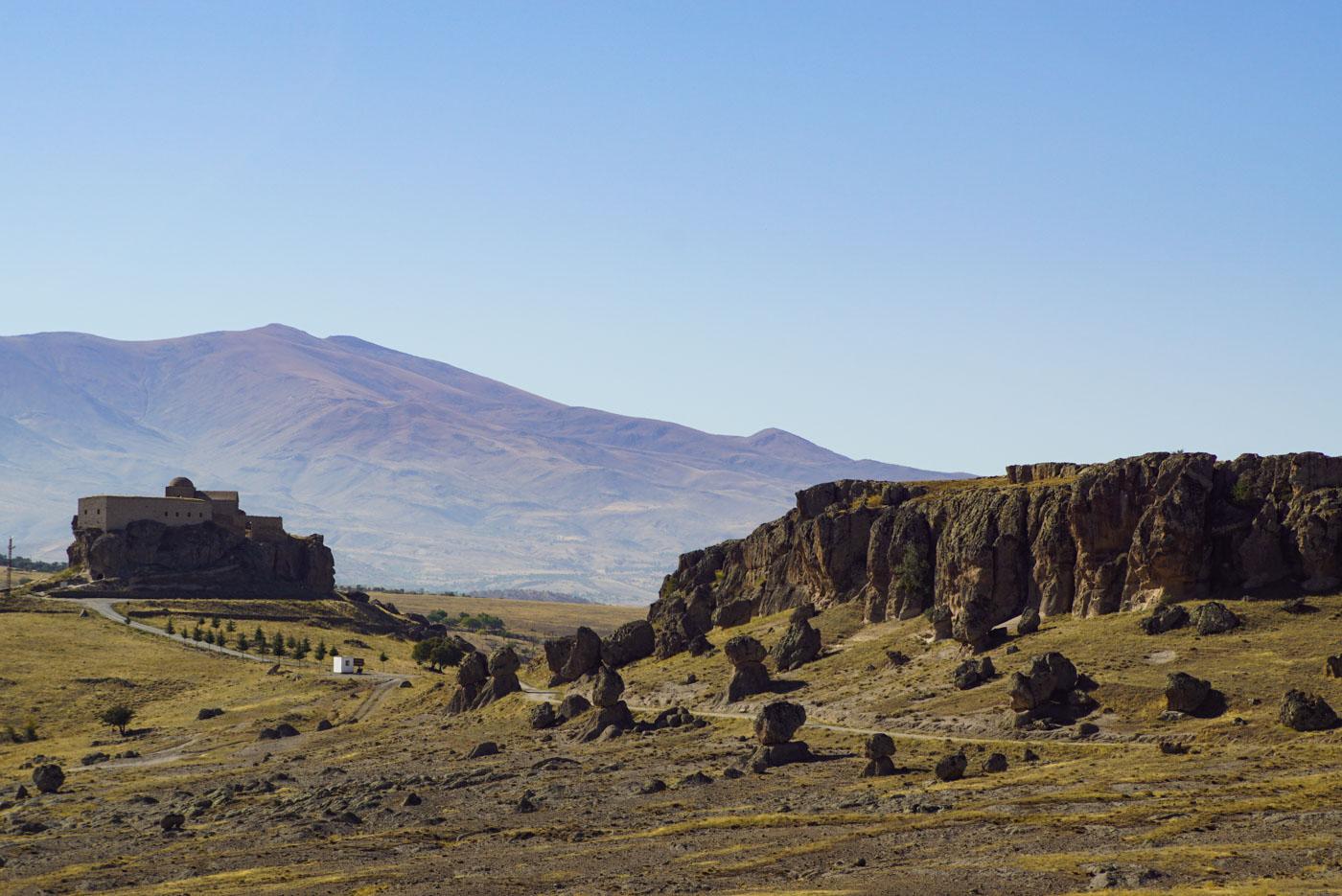 Blick auf das alte Kloster und dessen Zufahrtsstraße. Die Zufahrtsstraße wird von mächtigen Gesteinsbrocken gesäumt die auf Felsen stehen und es scheint als ob sie jeden Augenblick herunterfallen könnte und vorbeifahrende Autos zerquetschen.