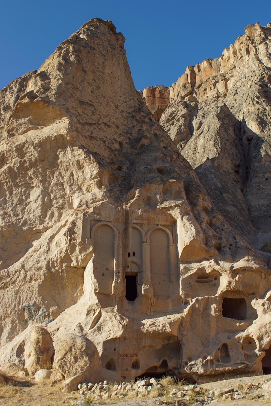 Zu sehen ist die in eine der Sandsteinformationen in Kappadokien ein beeindruckender Säuleneingang in den Felsen gehauen ist daneben befinden sich noch mehrere kleinere Höhlen