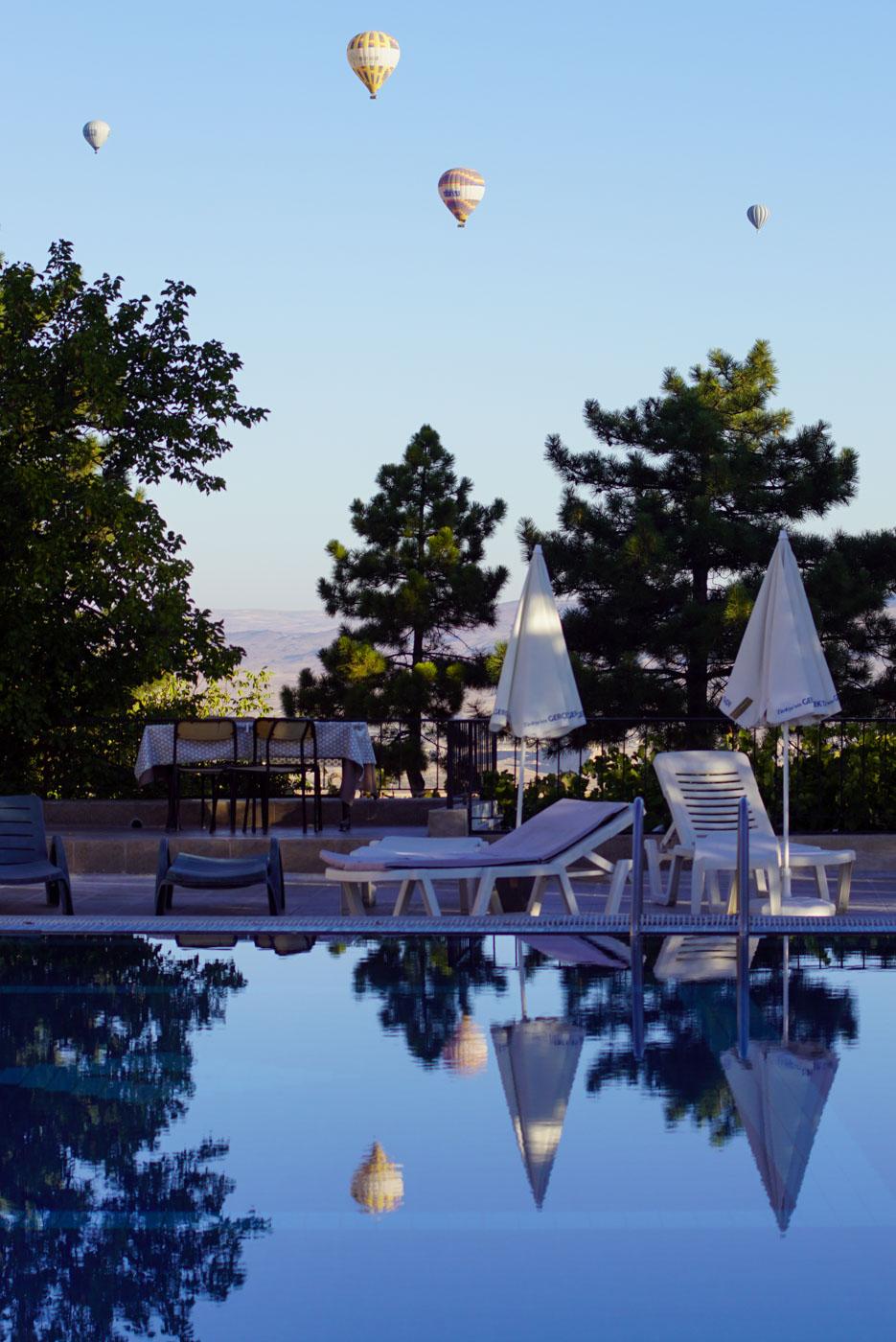 Blicke auf einen Swimmingpool in Göreme im Hintergrund sind drei Heißluftballons zu sehen die sich im Wasser des Pools wiederspiegeln.