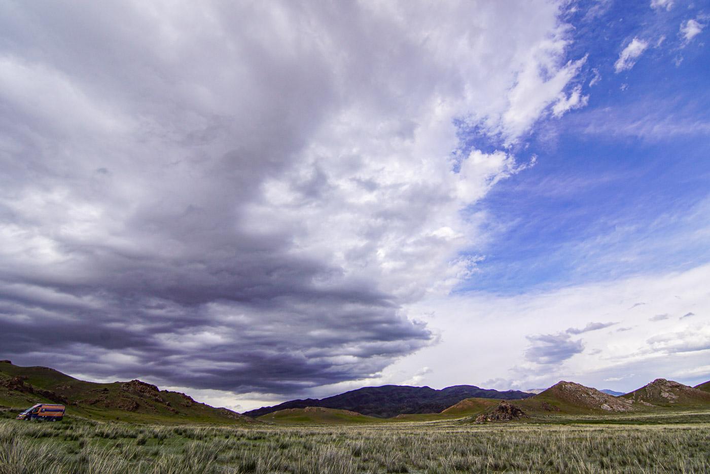 Zu sehen ist eine Aufnahme von unserem schlafplatz tuzkol Lake. Im Vordergrund erstreckt sich eine mit Steppengras bedeckte Fläche links außen ist unser Auto zu sehen dahinter erheben sich die Berge. Der Himmel ist zweigeteilt während rechts noch wunderschönes Wetter ist zieht von links eine dunkle sturmfront heran.