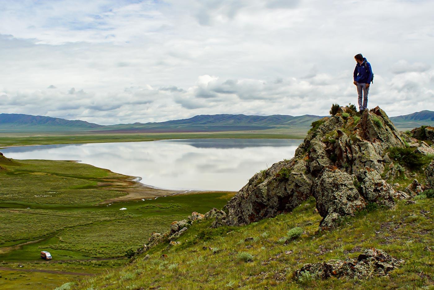 zu sehen ist wie Paul auf einem Felsvorsprung steht und in das Tal hinunter blickt dort auf einer grünen Wiese steht unser Auto im Hintergrund ist der See zu sehen in welchen sich die Wolken Spiegel dahinter wiederum erheben sich grüne Berge.