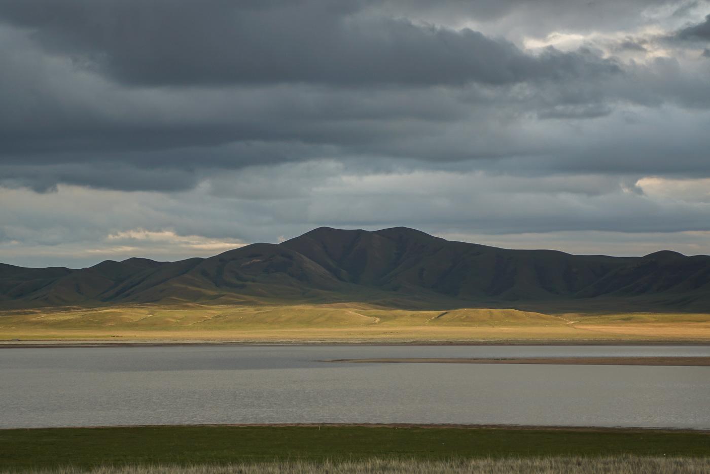 Zu sehen ist er See und dahinter erhebt sich von der Sonne noch bestrahlen grün gelbe Flächen. dahinter wird die Sonne schon von Wolken bedeckt und der sich dahinter erhebende Berg ist fast schwarz.