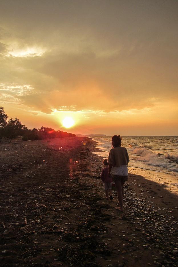 Lea und Luk gehen direkt an der Wasserlinie eines Strandes spazieren die Wellen brechen sich am Muschel übersätem Strand. Im Hintergrund geht die Sonne unter und färbt Wolken und Umgebung orange-rot